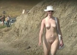 Naturist dame ambles on the beach just..